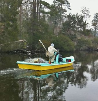 A strike-netter goes past a recreational angler's boat Feb. 4 in Onslow County's Stones Creek before closing off the creek to fishing by hook-and-line anglers.